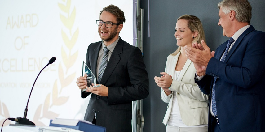 Business professional receiving a glass trophy