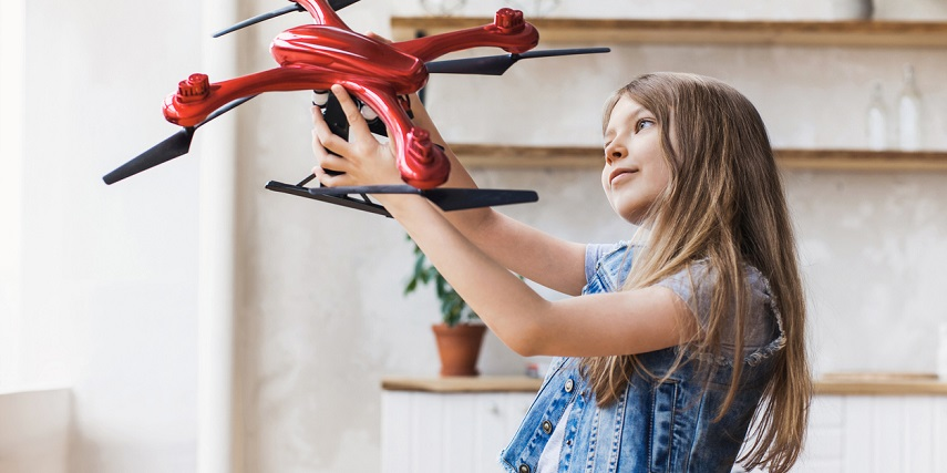 Child holding a custom drone made in a drone configurator