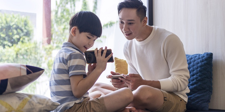 Dad and son looking at school supplies in a WooCommerce 360 product view tool on a phone
