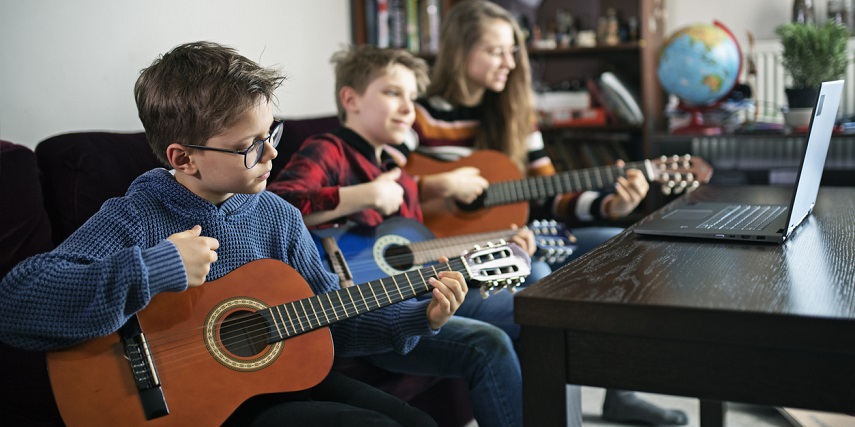 Group of children with custom-sized guitars ordered through a guitar configurator