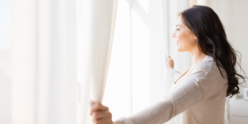 Homeowner opening curtains she designed through a product customizer