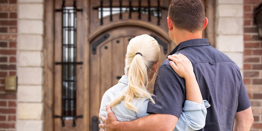 Homeowners looking at the newly installed front door they designed in a Magento product configurator
