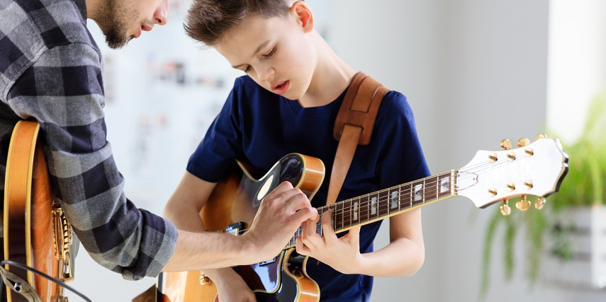 Kid learning how to play guitar on a custom-sized instrument made in a guitar configurator