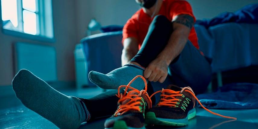 Man putting on custom running shoes he created through an Adidas shoe configurator