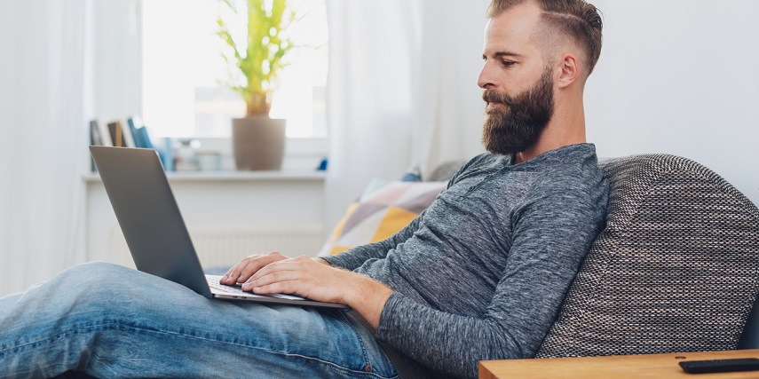 Man using a visual configurator while sitting on his sofa