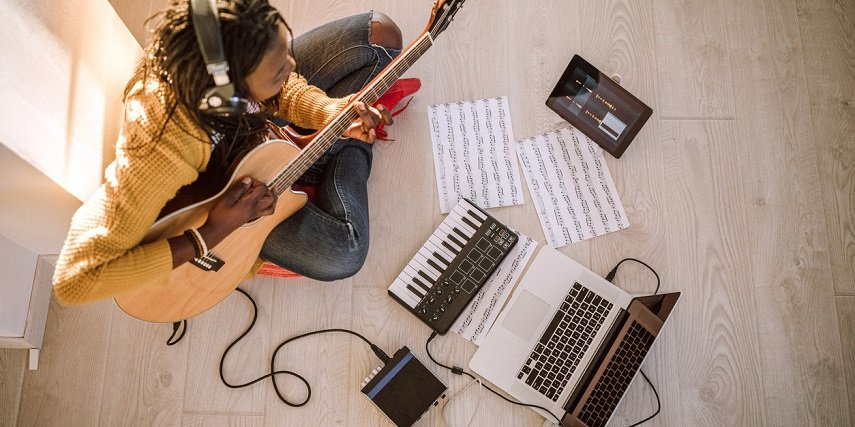 New guitar player taking virtual lessons and playing a guitar made in a guitar configurator