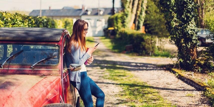 Shopper browsing through a 3D car customization online tool while leaning against their car