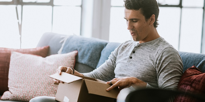 Shopper happily opening a package with a product he made through a Shopify product customizer