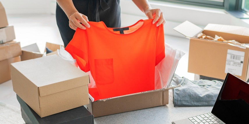 Shopper opening a delivered box of online clothes purchases