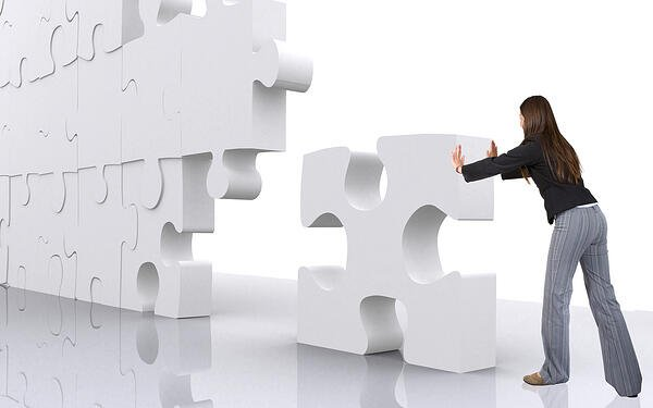 business teamwork - businesswoman building a puzzle which was made in 3d over a white background