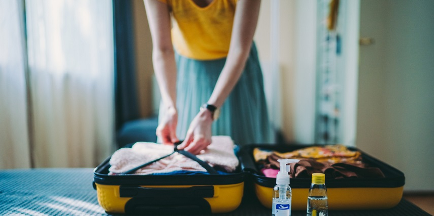 Traveler packing a yellow suitcase she created through a product customizer