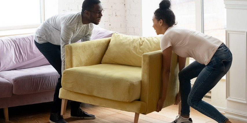 Two people moving a chair into their new living room