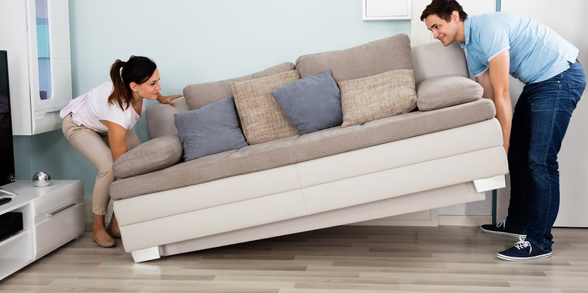 Two people moving a new couch they had ordered through a couch configurator