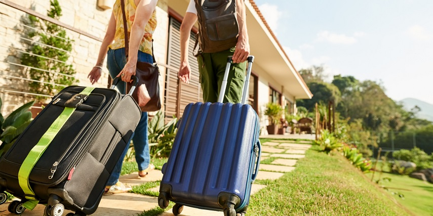 Two travelers with custom luggage they ordered through a WooCommerce product configurator