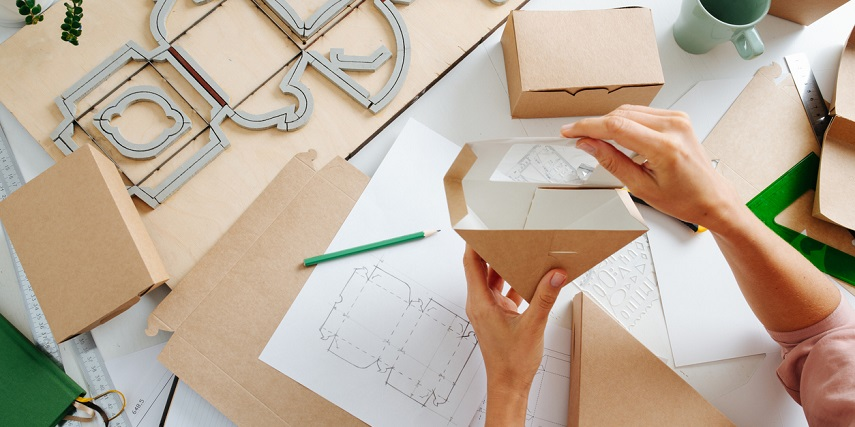 Woman assembling custom boxes created through a product configurator