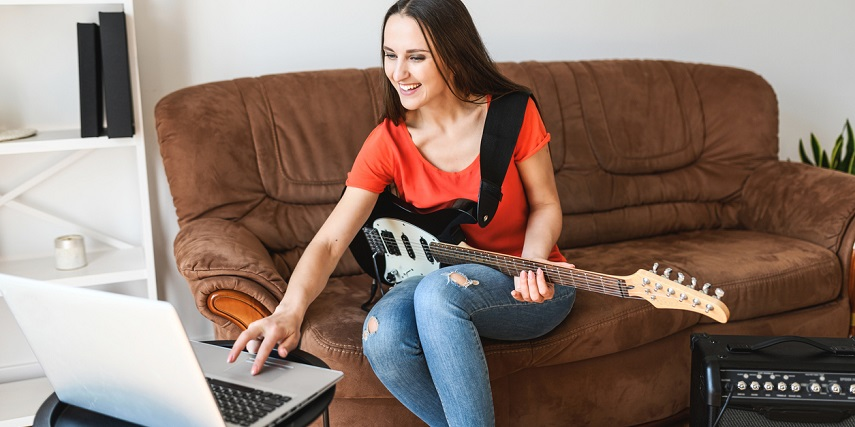 Woman learning online after ordering a guitar through a guitar configurator