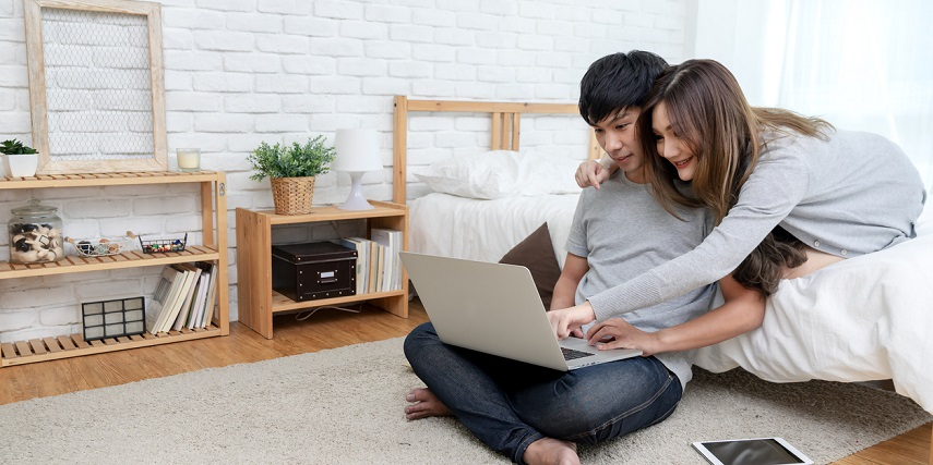 Young couple using a product customizer to add items to their wedding registry